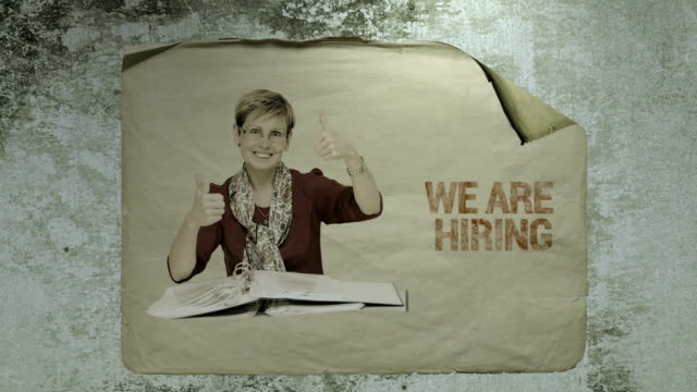 old paper job ad on a cement wall with a portrait of a staff member showing ok signs by her hands, imitation of camera shake and light flashes. busines recruitment concept. video