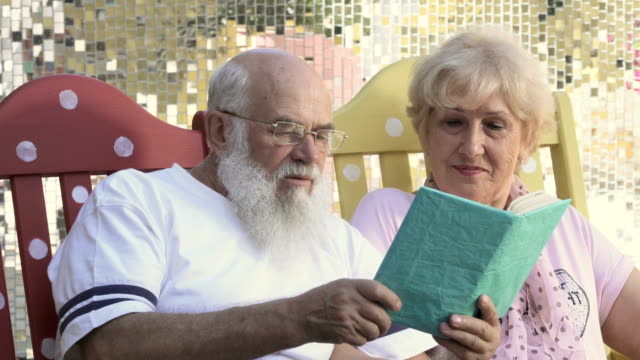 Old people reads book in rocking chairs, the husband kiss a wife in a cheek video