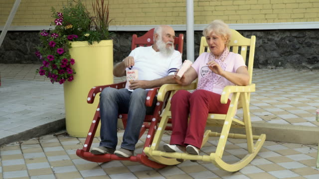 Old people swings in rocking chair and eats popcorn video