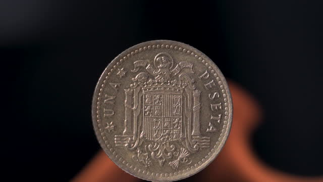 Old Peseta coin with the coat of arms of Franco's Spain formed by the eagle of San Juan with flames behind Old Peseta coin with the coat of arms of Franco's Spain formed by the eagle of San Juan with flames behind hot pockets stock videos & royalty-free footage
