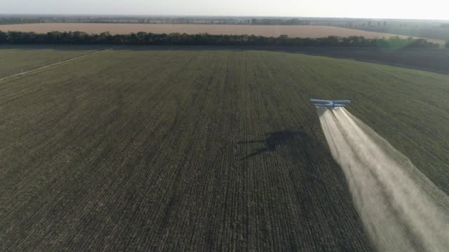 old propeller plane flies over green field with wheat and makes fertilizer spraying into agricultural video