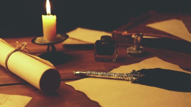 vidéos et rushes de vieux stylo plume sur papier parchemin à la chandelle - pots de bureau