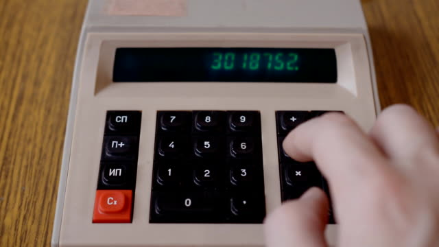 Old, retro or vintage calculator on table, made in USSR. Retro soviet calculator, Male hand pressing button