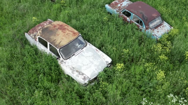 Old retro rusty abandoned cars in green grass, flight on drone above cemetery of vintage autos video
