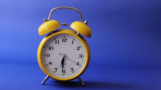 Old retro yellow alarm clock that triggers the alarm