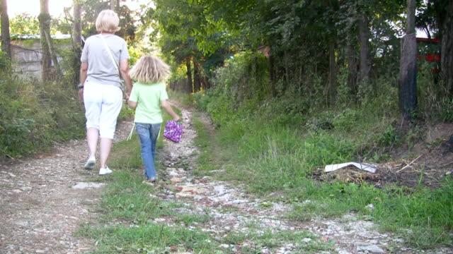 hd: vecchia strada - nonna e nipote camminare video stock e b–roll