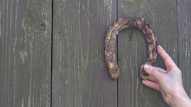 old rusty horseshoe on a wooden background. antique rusty horseshoe fixed on nails on old wooden surface. - horseshoe stock videos & royalty-free footage
