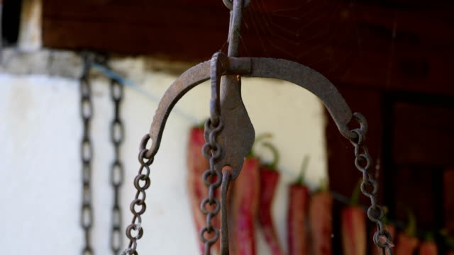 Old Rusty Iron Scale Weights with Dried Spicy Chili  Pepper Hangs on the rope