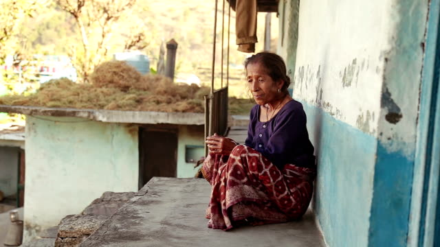 a old sad woman sits outside her house in uttarakhand, india - costume tradizionale video stock e b–roll