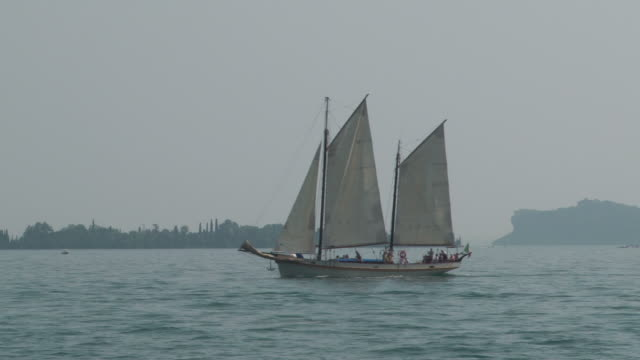 Old sailing vessel crossing the lake in thè morning mist