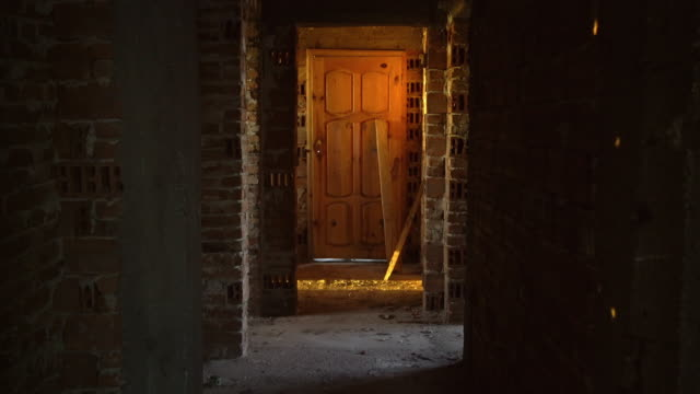 Old, scary, abandoned house interior. Wooden door at the end of scary concrete corridor. Architecture structure