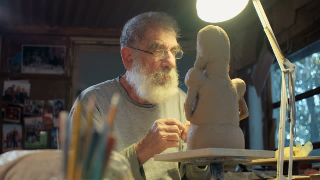 old sculptor working on a clay sculpture in his small studio - скульптура стоковые видео и кадры b-roll