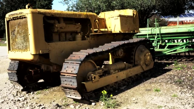 Netivot, Israel - February 12, 2019 : Old seeder attached to ancient crawler tractor with an open top. 4K