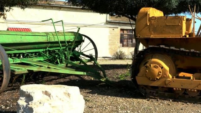 Old seeder attached to ancient crawler tractor with an open top. 4K