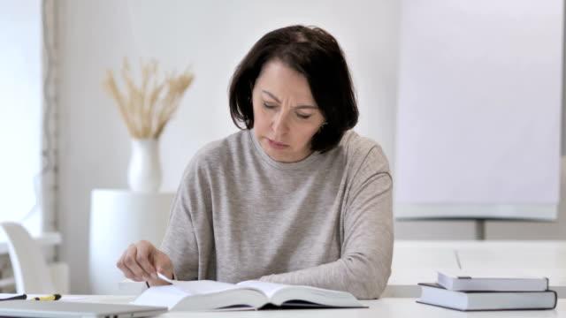 vídeos de stock e filmes b-roll de old senior woman reading book in office - trabalho de design