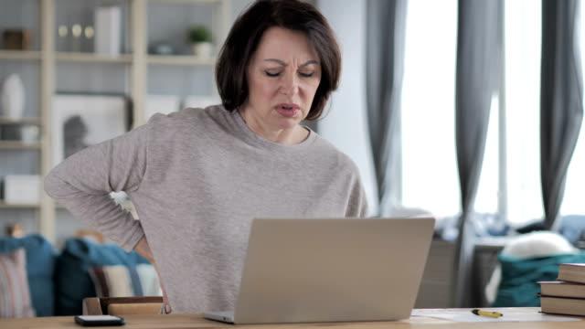 vídeos y material grabado en eventos de stock de mujer senior con dolor de espalda trabajando en ordenador portátil - columna vertebral humana