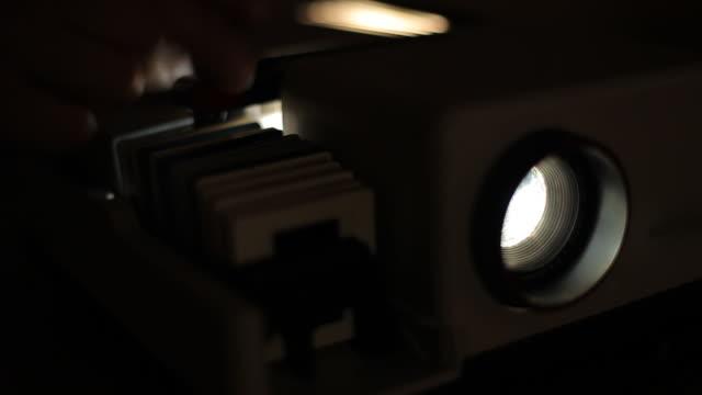 vídeos de stock, filmes e b-roll de projetor de slides antigo para fotos em close-up, mudando de cor e piscando luz. projetor de slides. - pré estreia