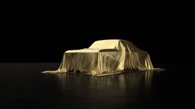 Old sports car covered with gold cloth.