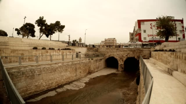 Old Stone Bridge under Ancient Canal Cars Cross Sanliurfa Cloudy Wintry Day video