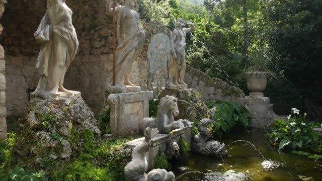 Old stone fountain in the botanical garden Trsteno, near Dubrovnik, Croatia. Statue of Neptune, goldfish in the water, blooming green water lilies. Film location Game of Thrones