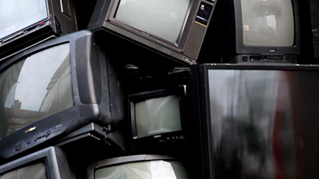 BANGKOK, THAILAND - JANUARY 8, 2015: old television electronic junk, garbage, rubbish, can be Recycle. broken TV stacked show in recycle and environmental theme fair. Great for background title, end credit video