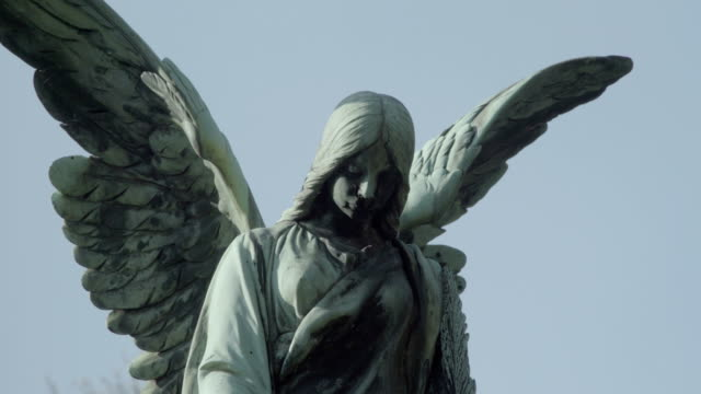 Old tombstone from 20th century with an angel on a sunny spring day. Defocus from angel. 4K in SLOG3. Close up. video