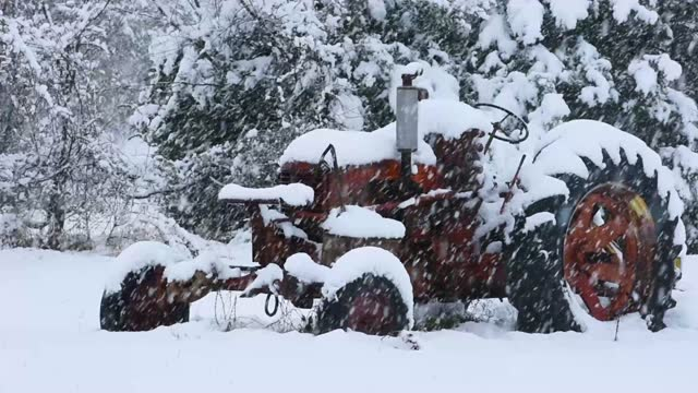 Old tractor out in a snow storm.