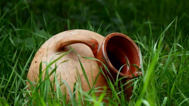 vidéos et rushes de vieille cruche en céramique traditionnelle dans l'herbe - picto urne