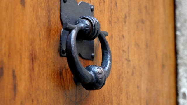 Old traditional forged metal door handle touched by a female hand in Prague video