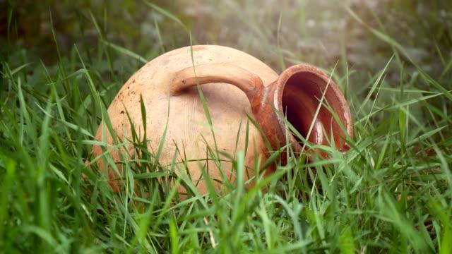 vidéos et rushes de vieux pichet traditionnel se trouvant dans l'herbe close-up - picto urne