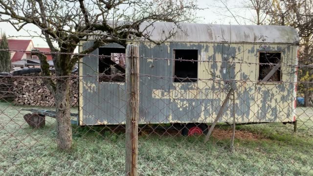 Old trailer in a garden behind a fence