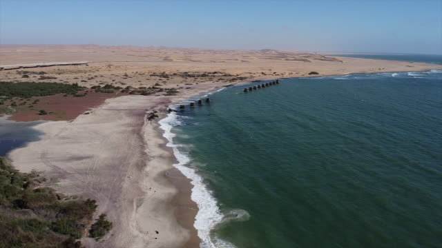 Old Train Bridge in Swakopmund Flight from Swakopmund towards the old train bridge. The pillars still remain as a reminder. This bridge was built over the Swakop river mouth. Skeleton Coast. Namibia. swakopmund stock videos & royalty-free footage