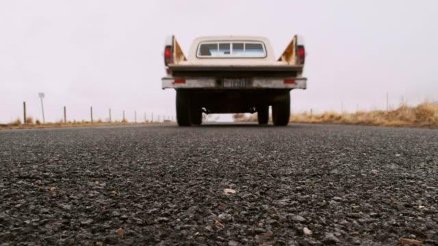 old truck on an empty road - passare davanti video stock e b–roll