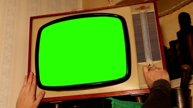 Old TV with green screen, retro TV in an old interior with a green screen Old TV with green screen, retro TV in an old interior with a green screen. Authentic Static On Old Fashioned TV Screen At Home Green Screen appliance stock videos & royalty-free footage