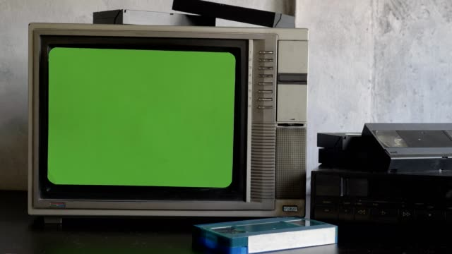 Old TV with green screen, video player and video cassettes on the table