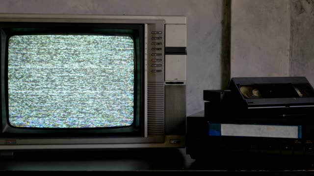 Old TV with signal bad interference, video player and video cassettes on the table video