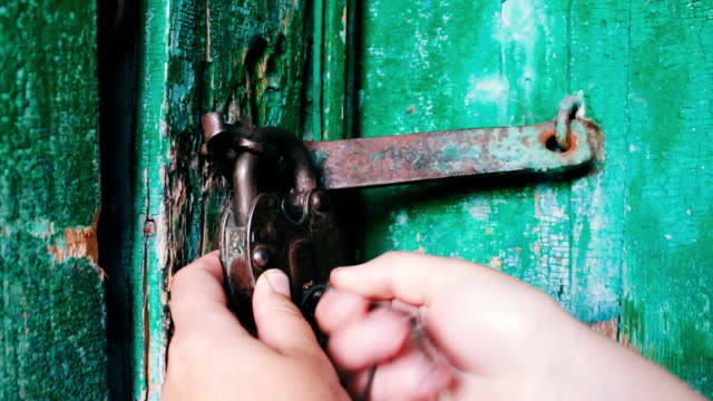 old vintage iron lock on the door with green paint peeled. female hand opens and closes lock - serratura video stock e b–roll