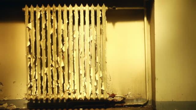 vídeos de stock, filmes e b-roll de radiador de vintage velho em casa abandonada - descascado