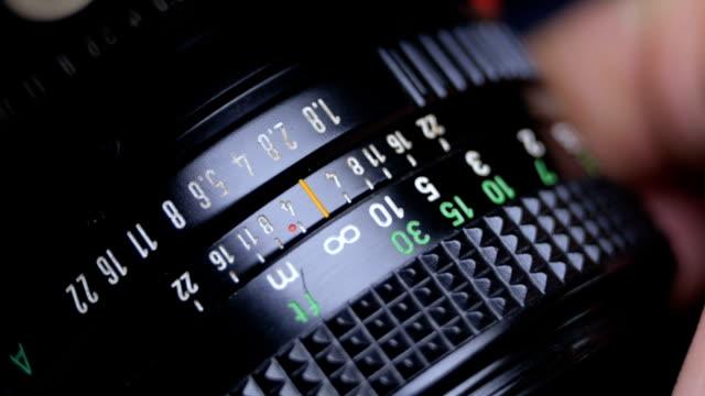 old vintage slr film camera lens while adjusting the aperture ring - analogico video stock e b–roll