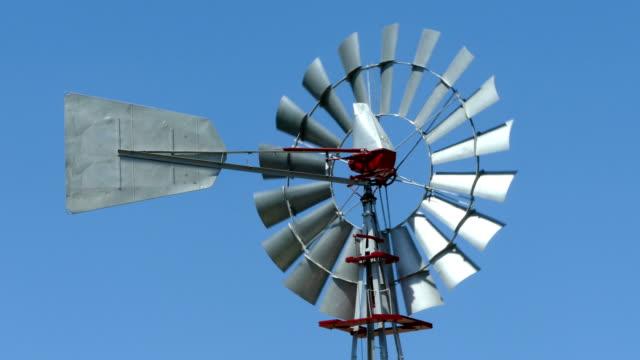 mavi gökyüzü arka plan ile güneşli bir günde dönen eski vintage tarzı yel değirmeni. - rüzgar enerjisi stok videoları ve detay görüntü çekimi