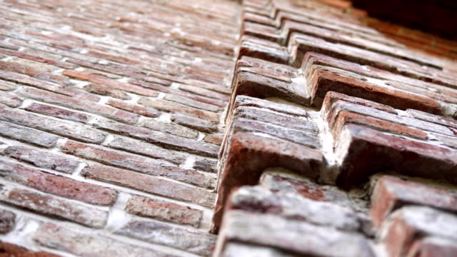 Old wall with ancient brickwork, brick background. Old wall with ancient crumbling brickwork, you can see the structure of the bricks. The camera is directed upwards and moves from left to right. brick stock videos & royalty-free footage