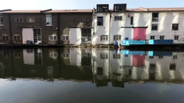 old warehouse buidlings in waterside canal dock with barge - victorian architecture stock videos & royalty-free footage