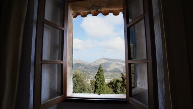 Old window. Time Lapse View through an old window in Spain. Clouds passing mountains. lockdown viewpoint stock videos & royalty-free footage