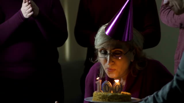 Old Woman Blowing Out Cake Candles On 100 Birthday Party Volunteers Support Stock Video More Clips Of Adult