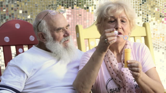Old woman blows bubbles sitting in rocking chair video