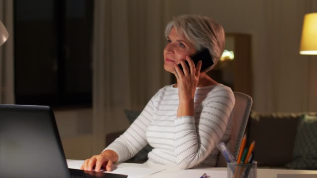 old woman calling on smartphone at home at night - vídeo