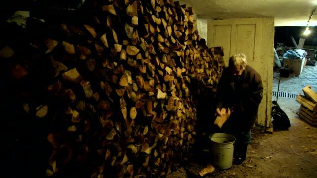yaşlı kadın yakacak odun toplama - şömine odunu stok videoları ve detay görüntü çekimi
