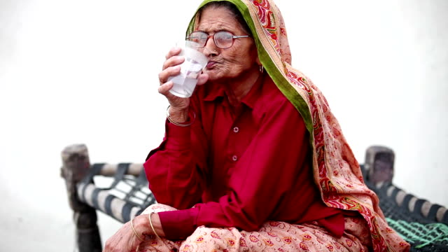 Old woman drinking cold drink, time lapse Full HD : Elderly woman of Indian ethnicity sitting on a cot (Charpai) and drinking cold drink. sari stock videos & royalty-free footage