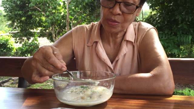 Old woman eating congee or rice porridge with minced pork