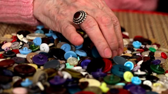 Old woman graded buttons on the table video